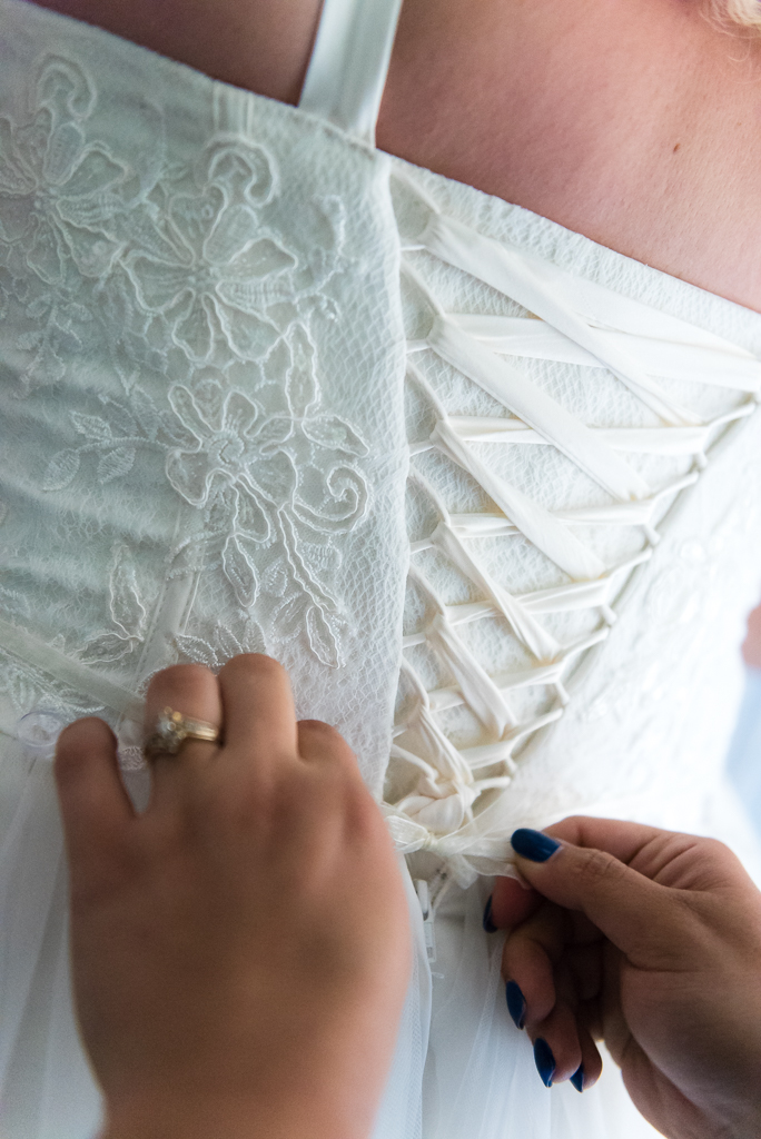 A bridesmaid adjusts the laces on the back of a bride's wedding gown.