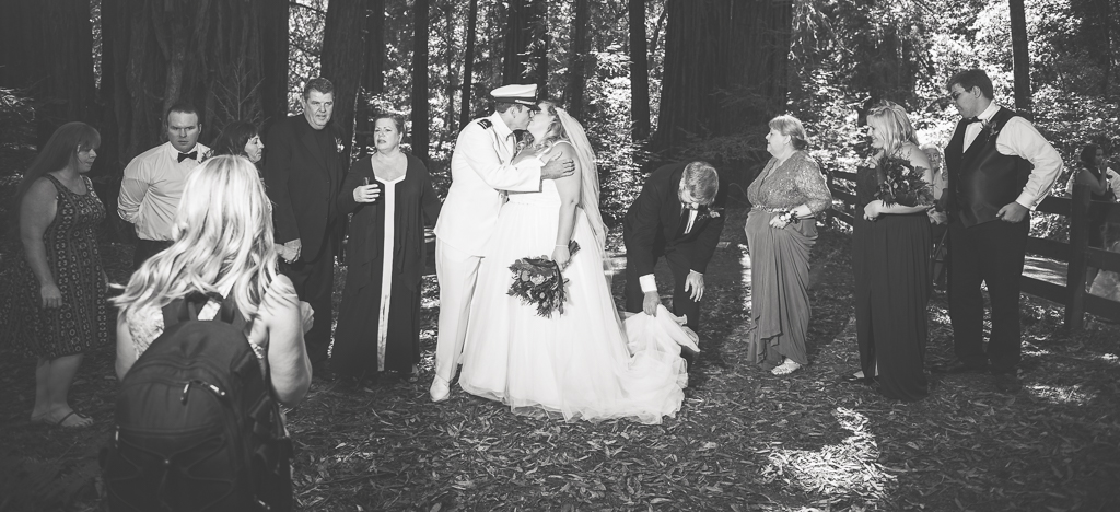 Black and white of a bride and groom kissing as family members align for a family portrait.