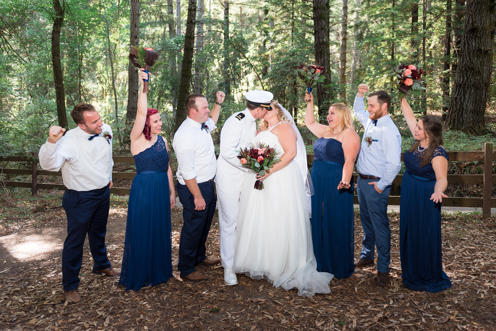 A bridal party cheers on the kissing bride and groom.