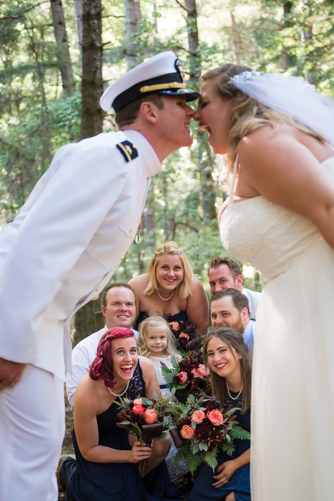 A crouching bridal party looks on the kissing bride and groom.