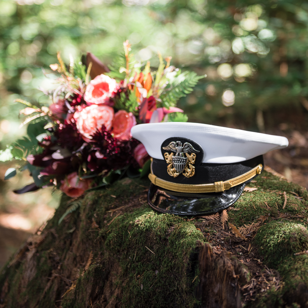 Detail shot of a bouquet and Navy visor hat resting on a tree stump.