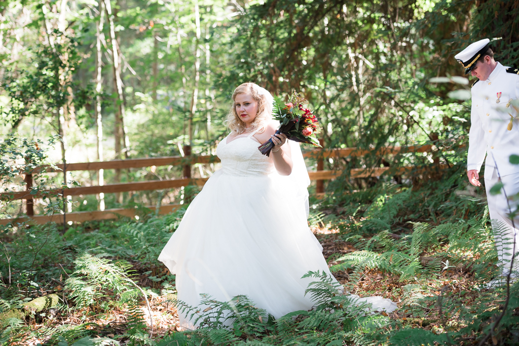 A bride walks ahead of her groom into the woods while clutching a bouquet.