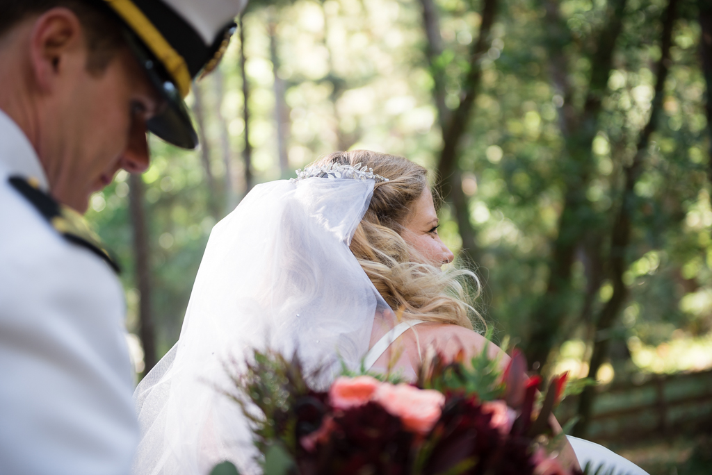 A groom holds the bouquet for his bride.