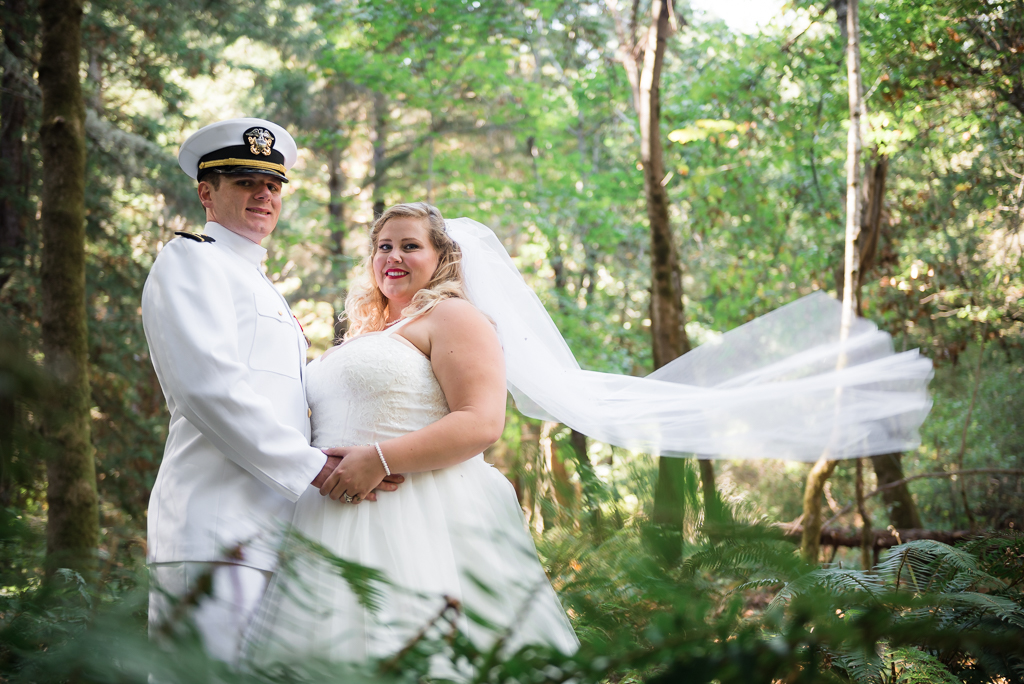 A bride and her Navy Officer groom stand together as her veil blows in the wind.