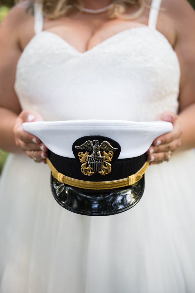 A bride holds her groom's Navy cover.