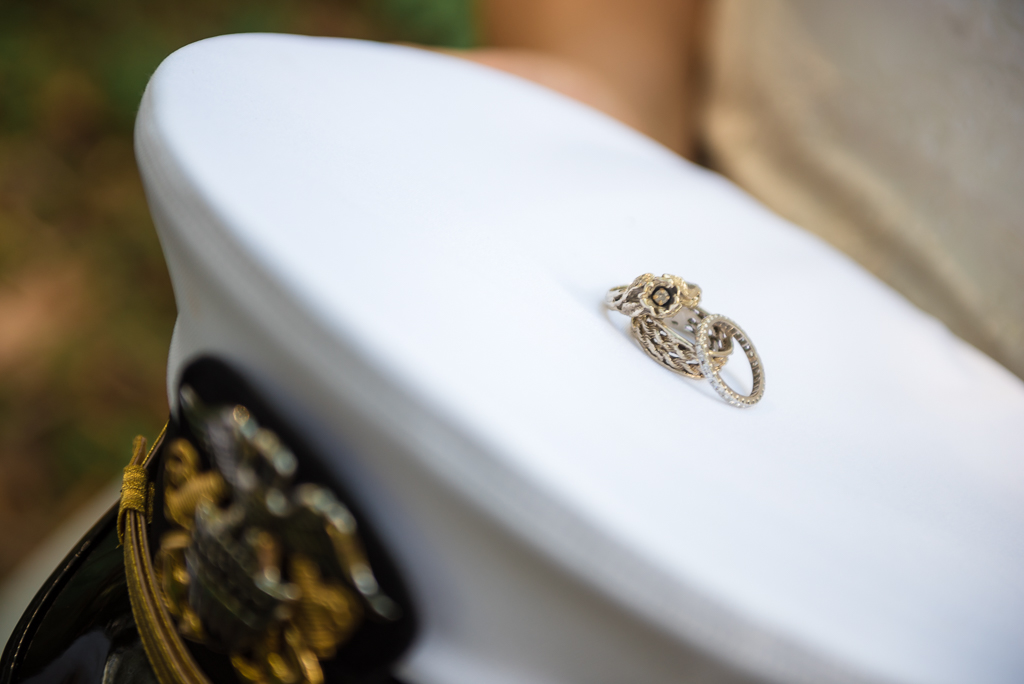 Wedding rings placed on top of a Navy hat.