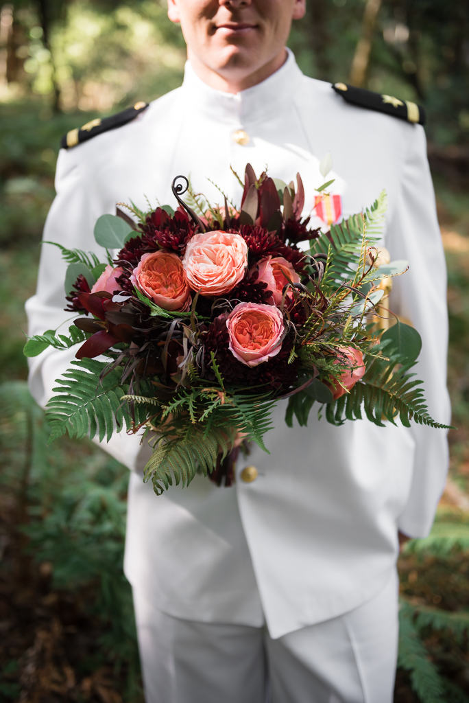 Close up of a fern bouquet, held by a groom wearing his Navy white uniform.