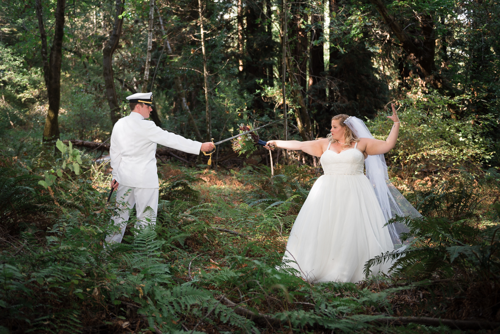 A bride and groom pretend to duel in a redwood forest.