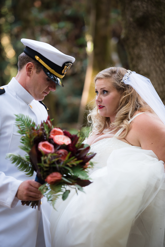 Photograph of a bride looking on at her groom.