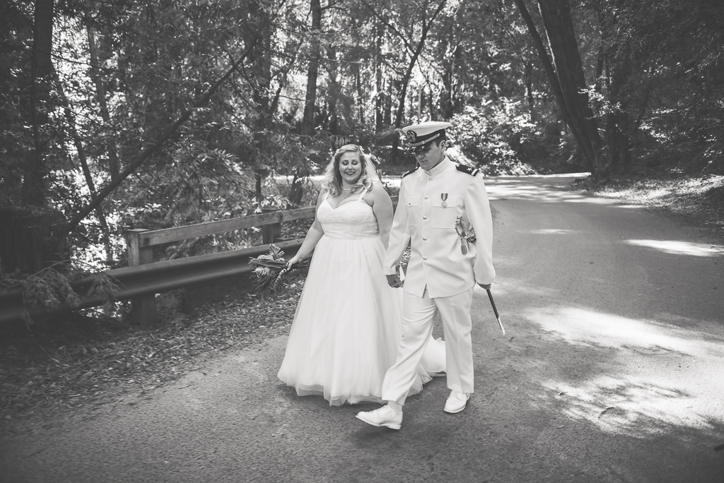 Black and white photo of a bride and groom dressed in his Navy uniform walking down a street in the forest.