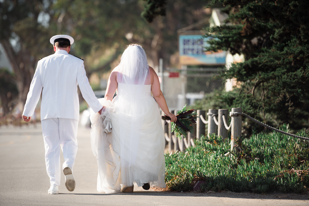 A groom holds the train of his bride's wedding gown as they walk down the road.