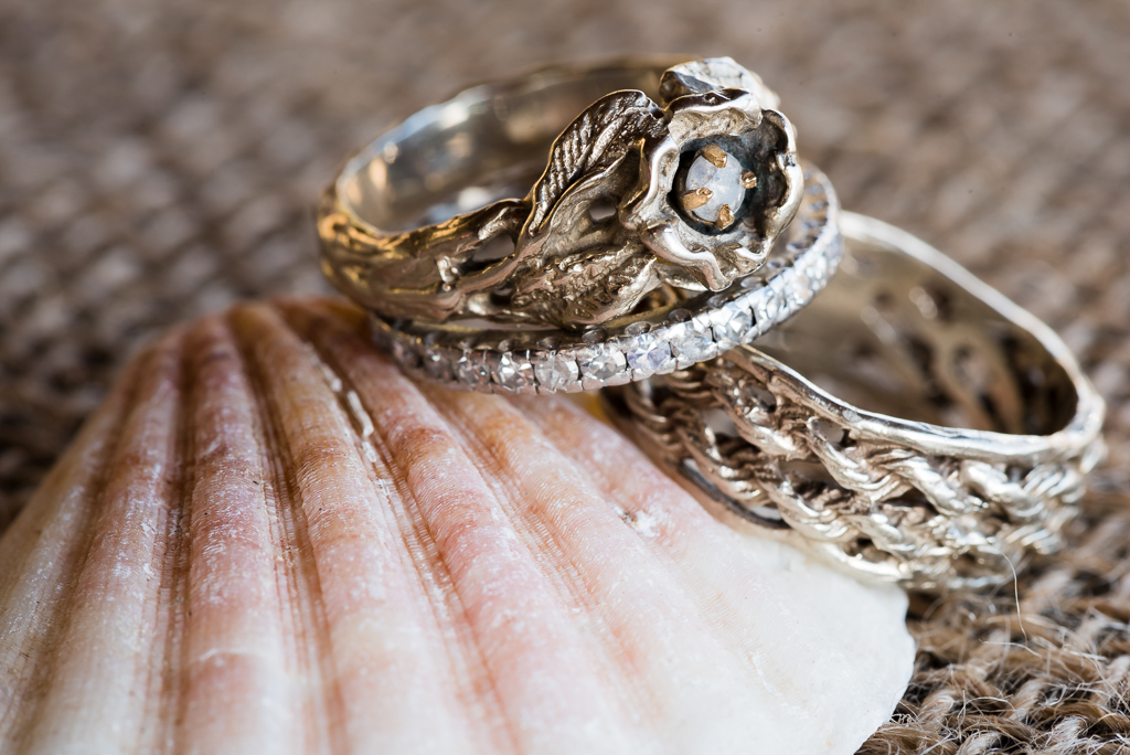 Wedding rings placed atop a clam shell.