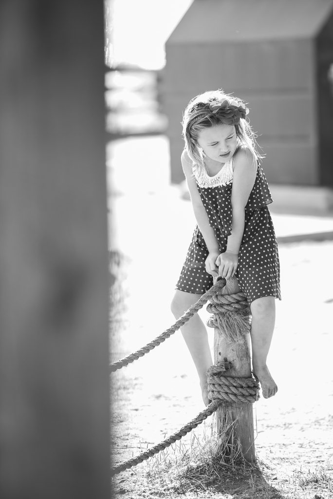 Black and white photo of a young girl sitting on a wooden post at a wedding reception.