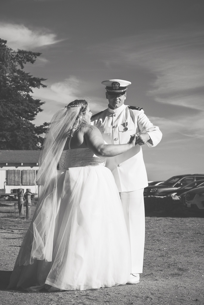 Black and white photo of a Navy serviceman groom dancing with his bride.