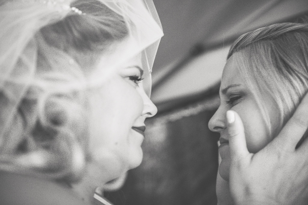 A black and white photo of the bride's sister crying when she sees the bride.