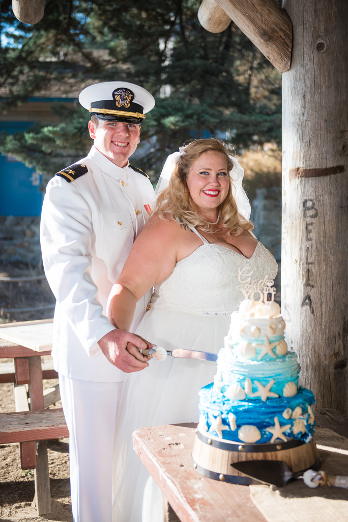 A bride and groom stand by their nautical-themed wedding cake.