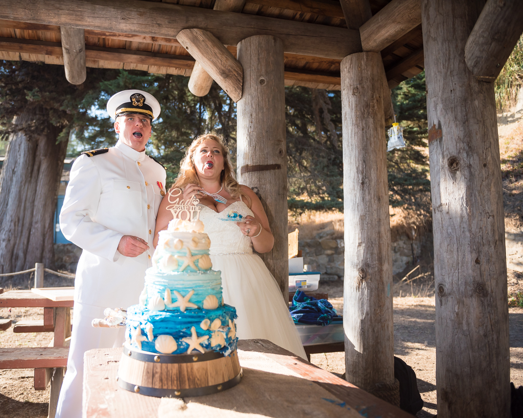 A bride and groom stick out their blue tongues after tasting their wedding cake.