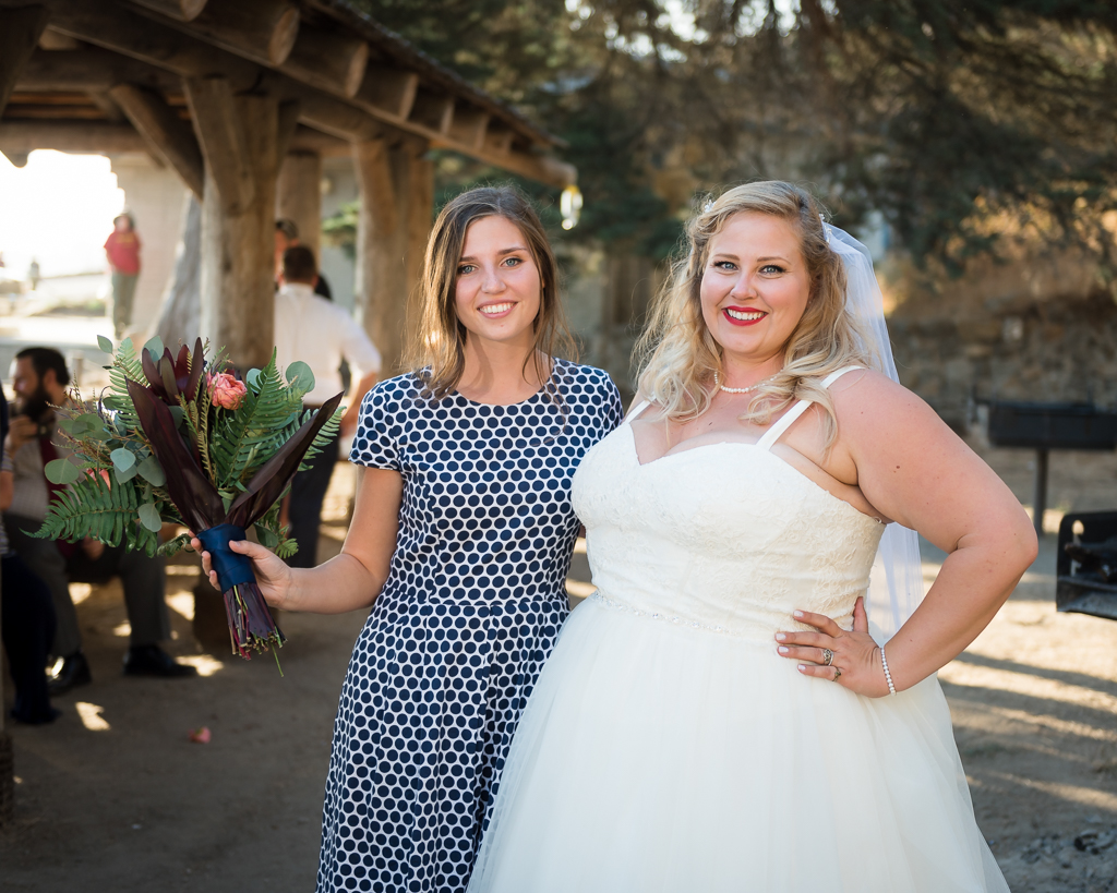 A bride and the friend that caught the tossed bouquet.