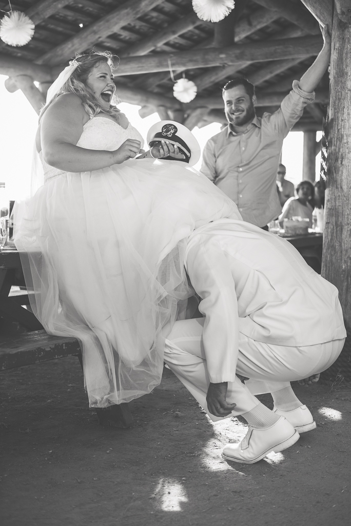 Black and white photo of a groom fetching his bride's garter.