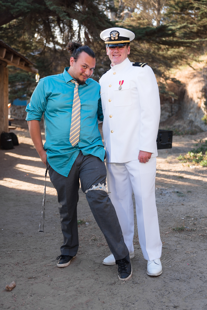 A groom stands next to the bachelor who caught the tossed garter.