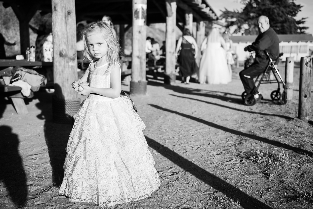 black and white photograph of a flower girl at a beachfront wedding reception.