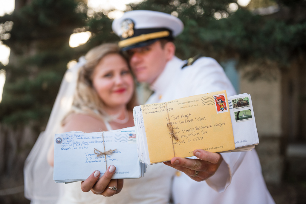 A bride and groom pose with bundles of letters they sent eachother while the groom was away at Navy basic training.
