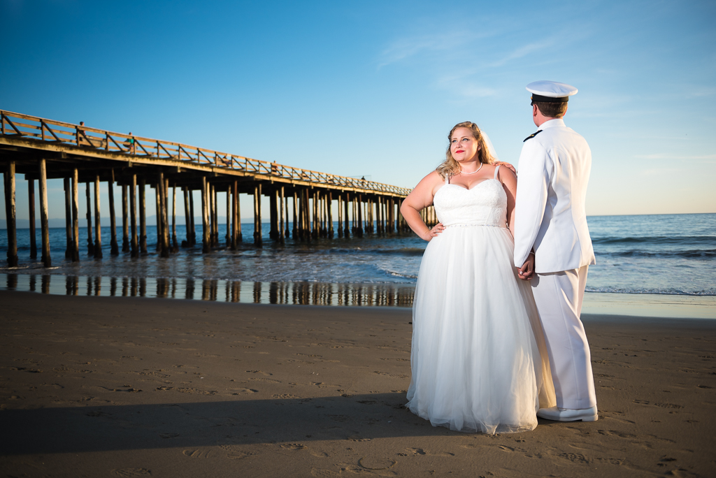 Photo of a bride and groom in front of the pier at Seaside State Beach in Aptos, CA.