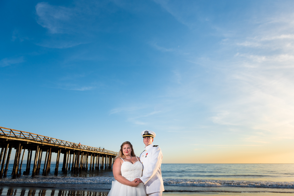 A photograph of a bride and groom in front of a vibrant ocean sky in Aptos, California.