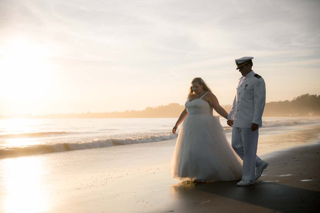 A natural light photo of a bride and groom walking down the beach together.