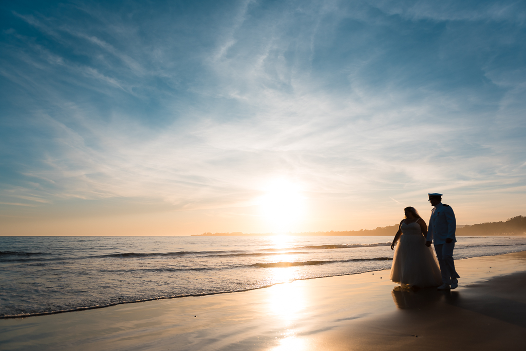 A sunset photo of a silhouetted bride and groom walking along Seacliff State Beach.