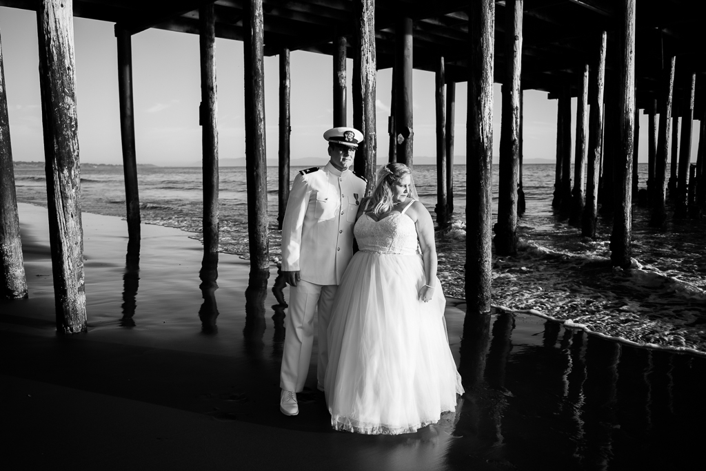 Black and white photograph of a bride and groom standing beneath a pier.