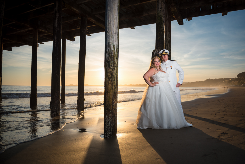 A bride and groom pose for a bridal portrait beneath the pier at Seacliffs State Beach.