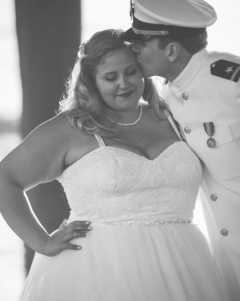 Black and white photograph of a groom kissing his bride on the side of her head.