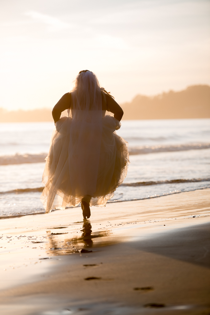 A bride wanders off into the waves while wearing hr wedding gown.