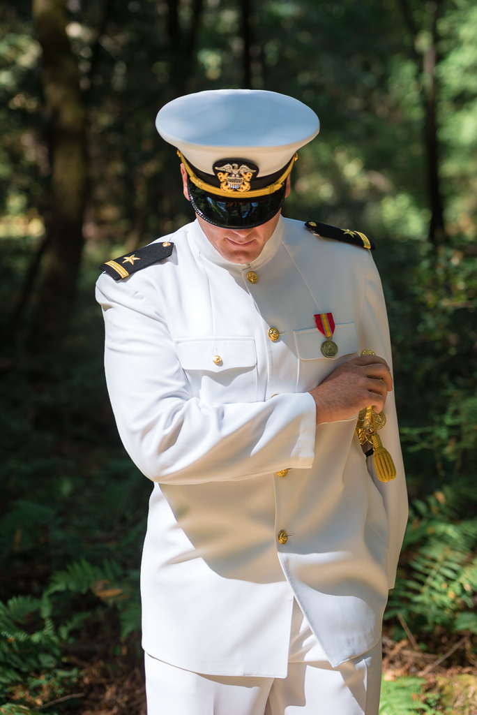 Portrait of groom dressed in his Navy whites against a forest backdrop.
