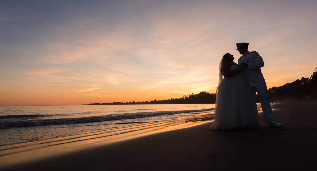 SIlhouette of a bride and groom against a sunset along the beach in Northern California.