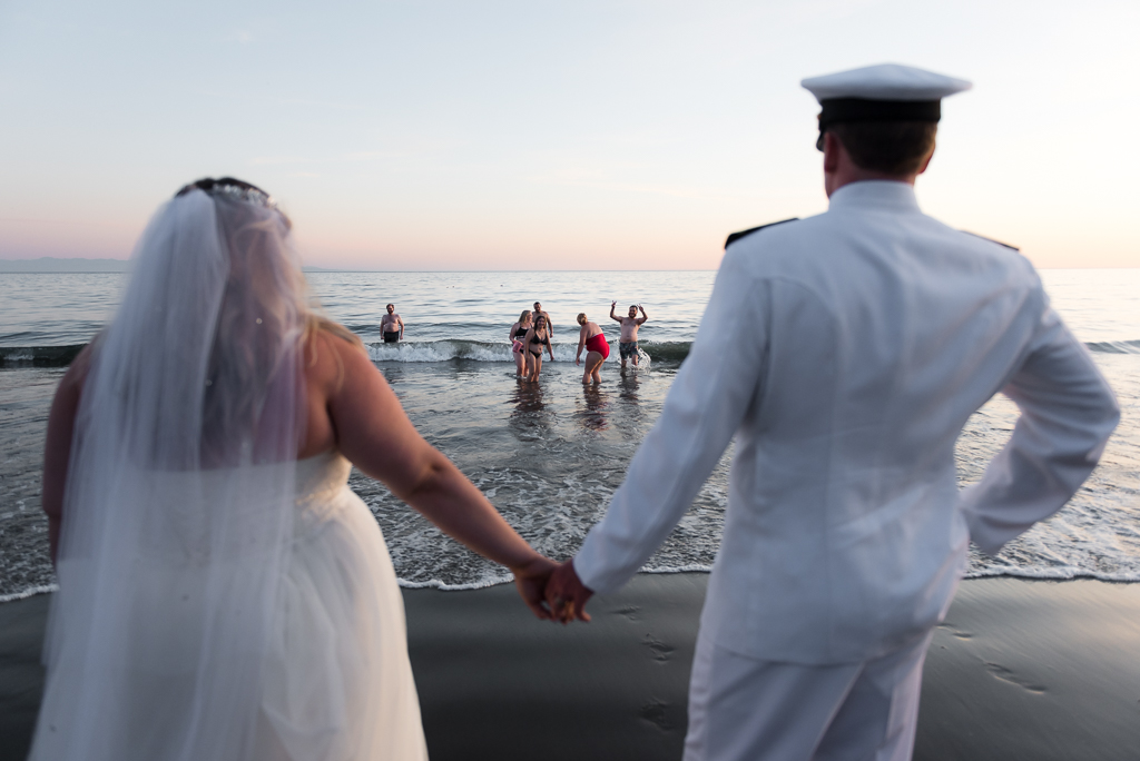 A bride and groom hold hands as they watch their friends play in the ocean.