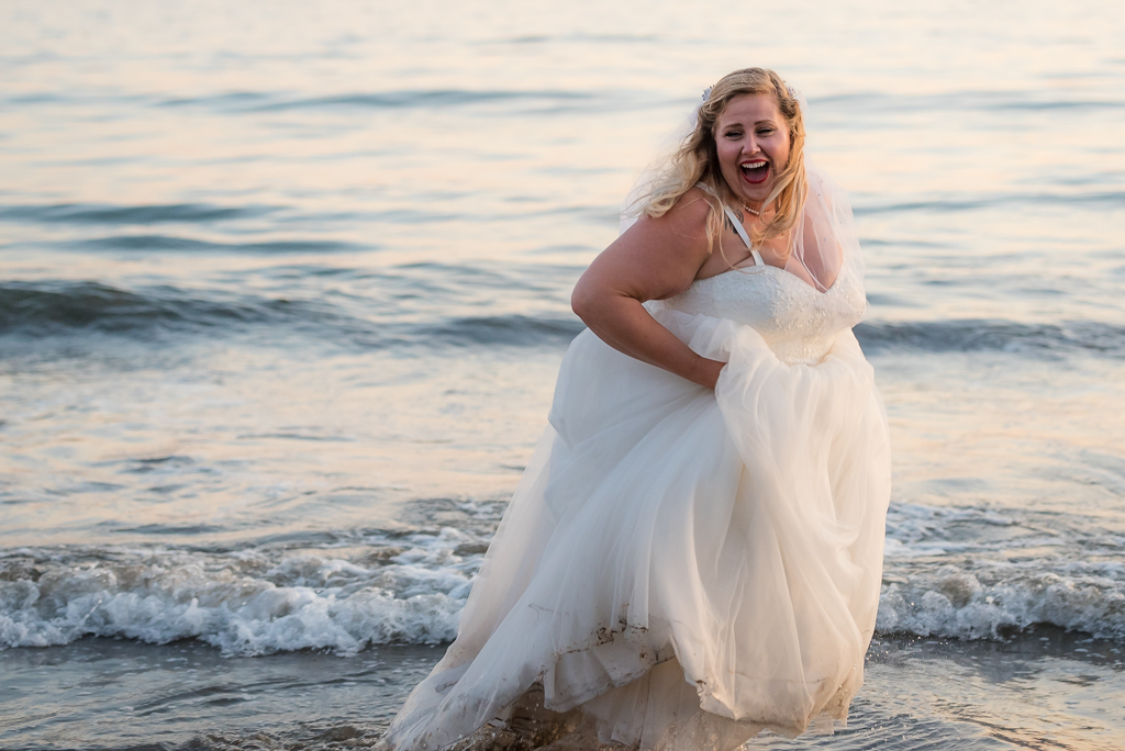 A bride hikes up her gown as she runs through the waves.