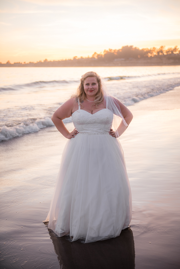 A bridal portrait taken while the bride wears her gown at the edge of the beach.