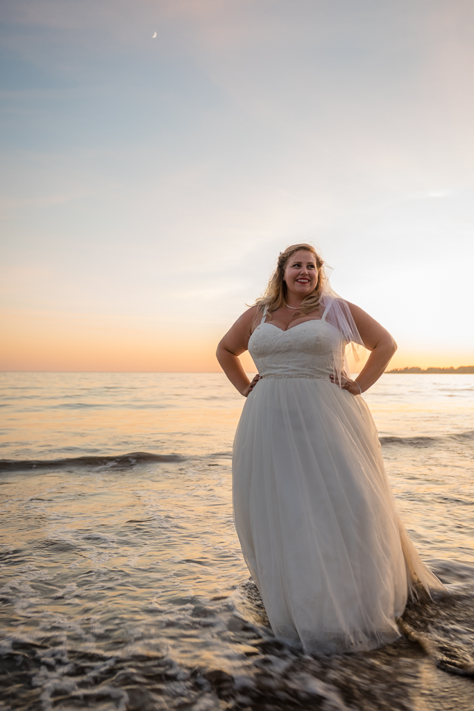 A bride poses for a portrait while standing in some shallow waves.