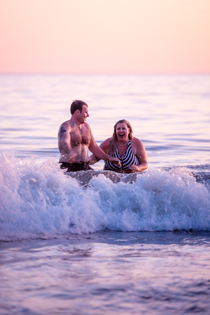 A bride and groom play in the ocean at Seaside Cliffs State beach in Aptos, CA.