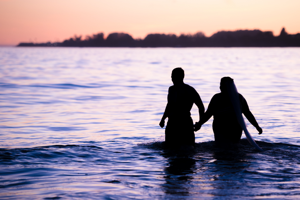 A silhouetted image of a new bride and groom walking into the ocean at Seaside Cliffs State Beach.