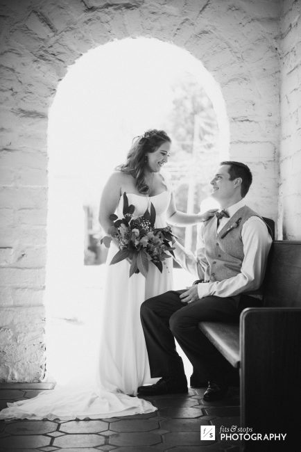 Black and white photograph of a bride gazing into the eyes of her groom as he sits on a church pew.