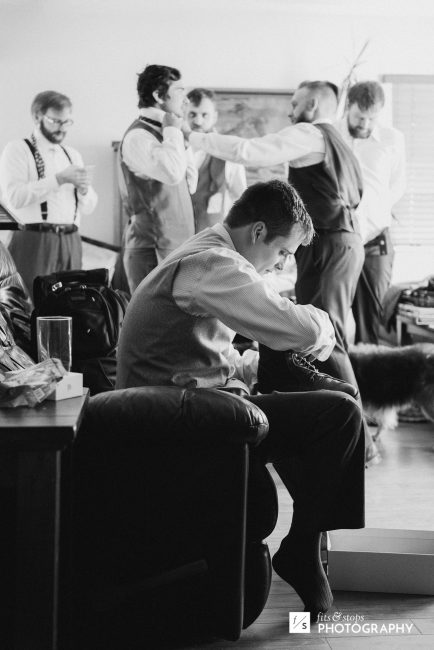 Black and white photograph of a young groom putting on his shoes in preparation for his wedding ceremony.
