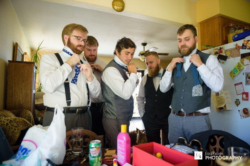 A photograph of five groomsmen circling a smartphone to watch a video about how to tie their bow ties.
