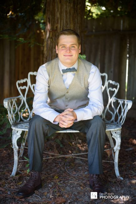 A young groom sits on a metal chair against a background of redwoods.