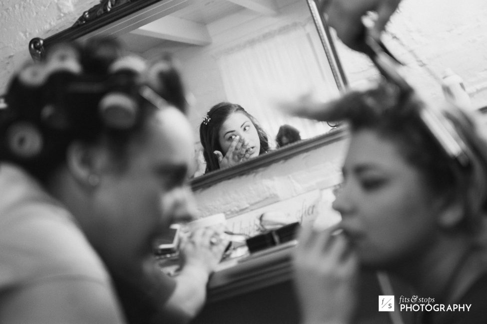 Black and white photograph of a bride and her bridesmaids getting ready for the wedding.