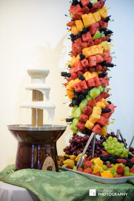 A table with a white chocolate fountain and a tower of fruit skewers, stretching out of the frame.