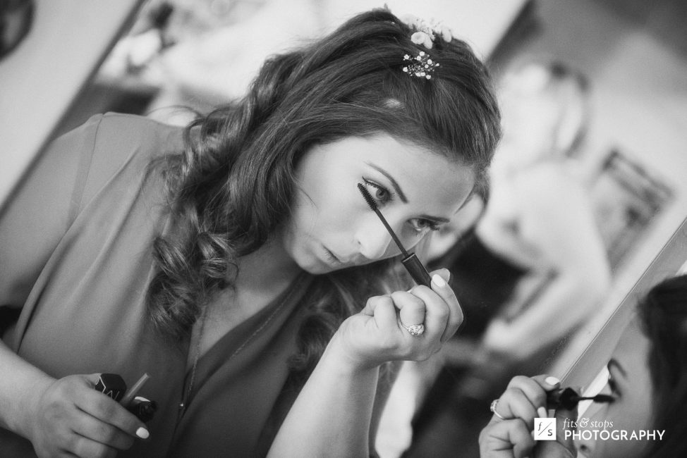 Black and white photograph of a young bride applying eyeliner.