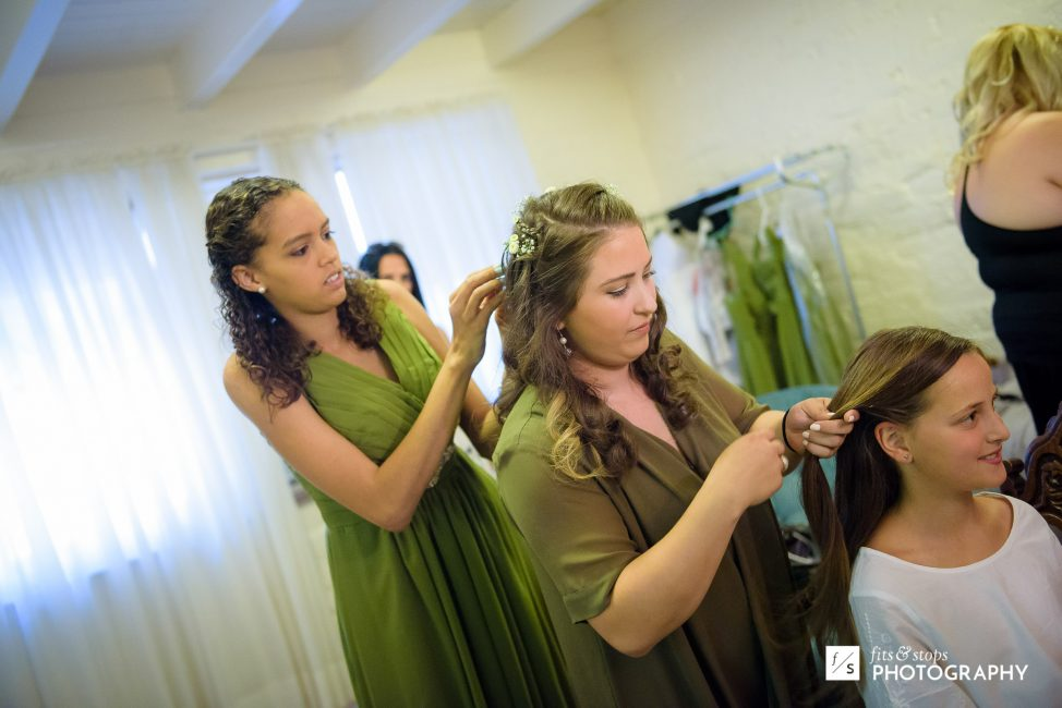 Photograph of a bridesmaid attending to the bride while the bride attends to the flower girl.